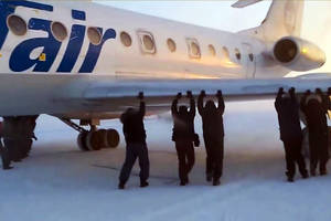 Passengers free their jet after it freezes to the runway